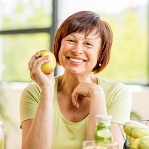 Smiling older woman holding an apple