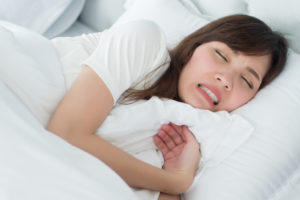 Woman grinding her teeth while sleeping