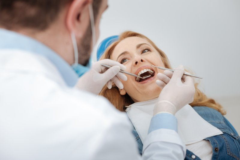 a woman having her teeth checked by her dentist