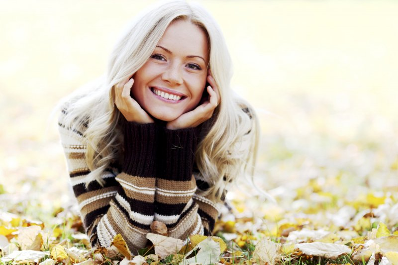 a young woman lying in the leaves and smiling