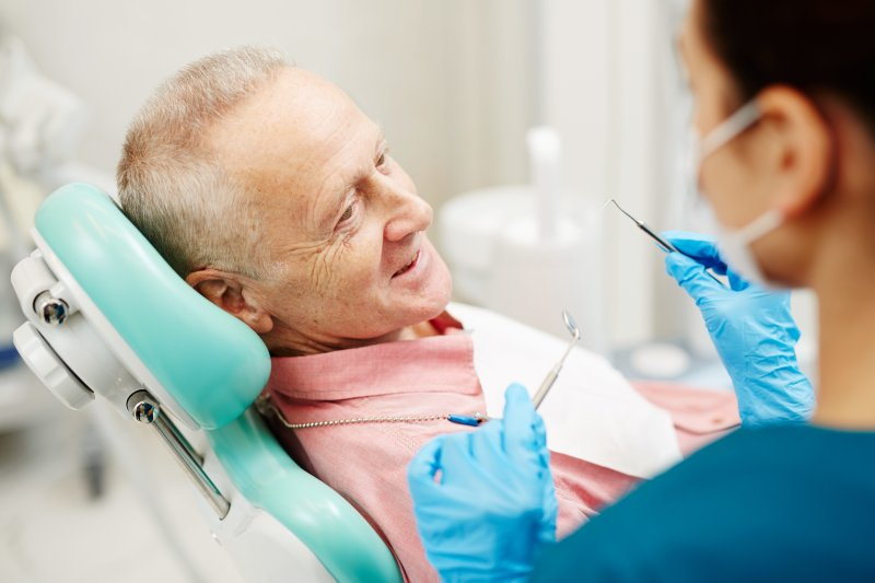 an older gentleman having his teeth checked at the dentist's office