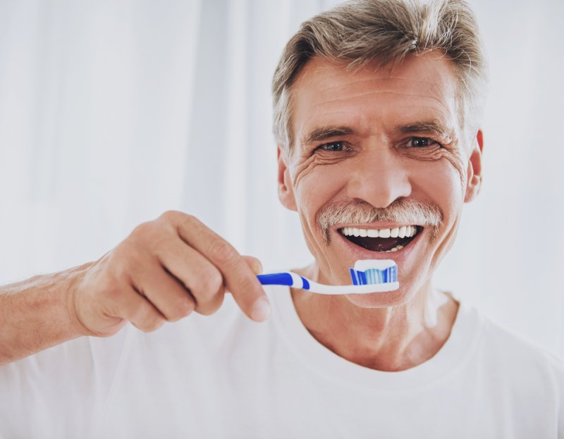 an older gentleman preparing to brush his teeth as part of his dental bridge maintenance routine