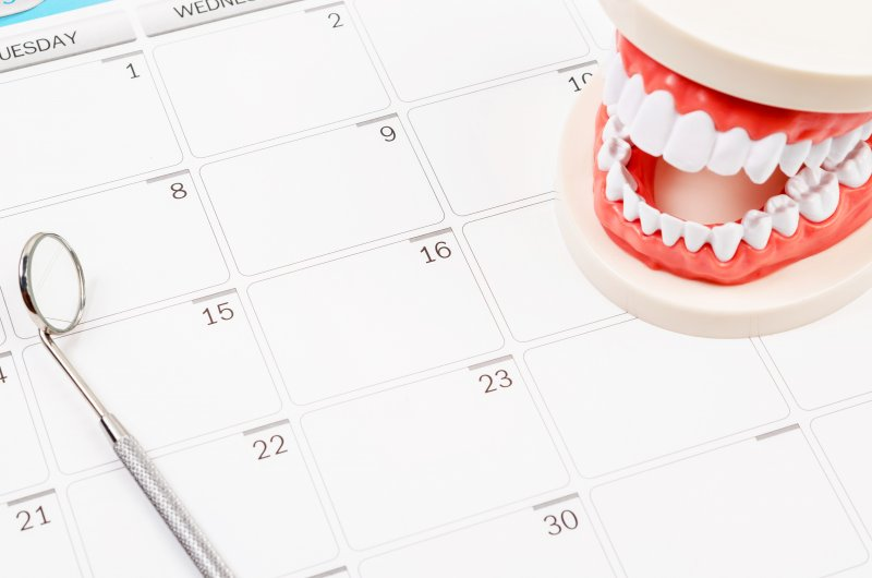 a calendar for a dentist in North Naples with a mouth mold and dental mirror instrument laying on top