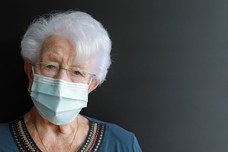 an elderly woman wearing a  face mask and glasses