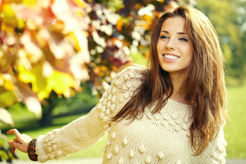 a young woman standing outside among the fall leaves and smiling