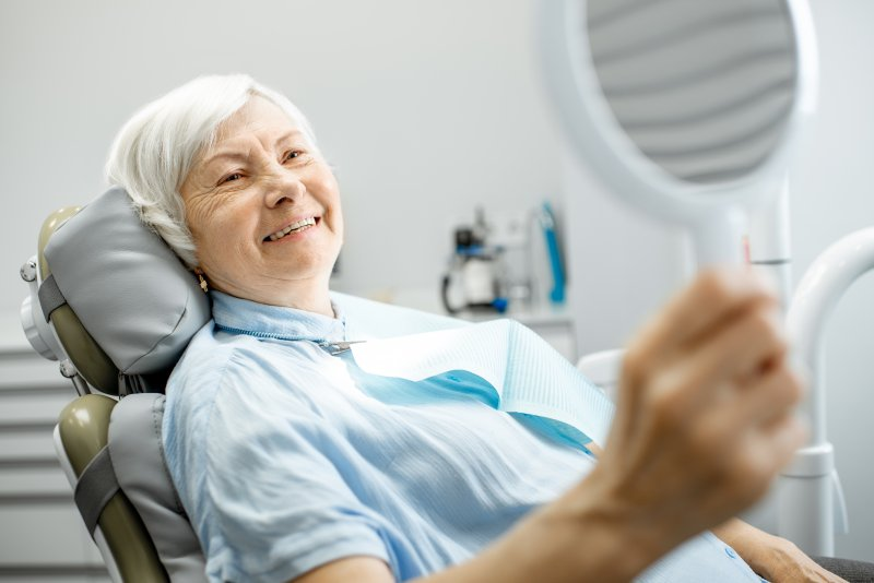 an older woman sitting in dentist's chair pleased with her new dental implants