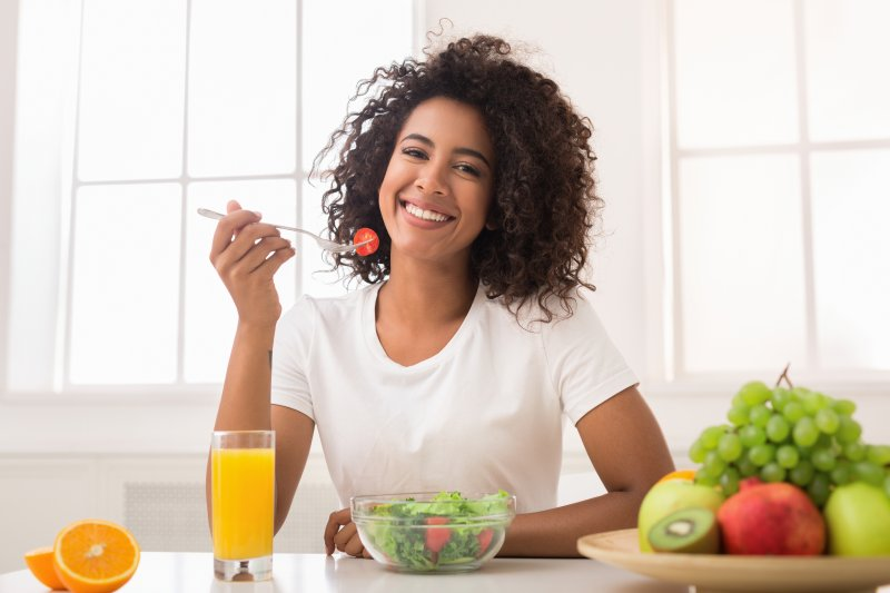 a young woman eating a salad and smiling while surrounded by various fruits and orange juice