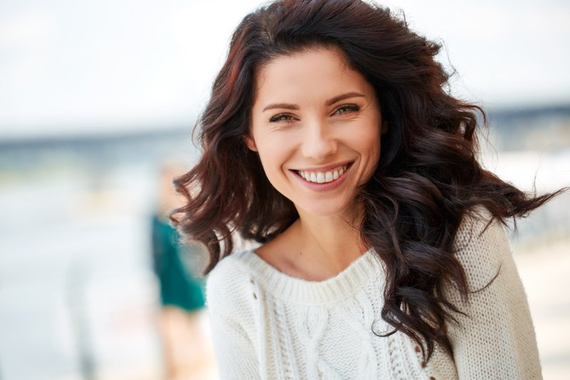 a young woman wearing a cream sweater and showing off her brighter smile